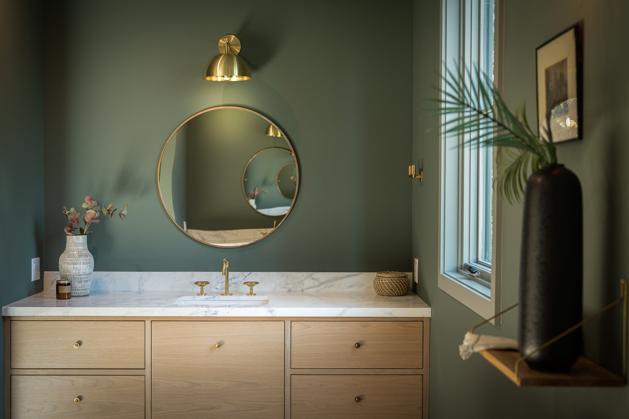 Bathroom vanity with round mirror and green walls